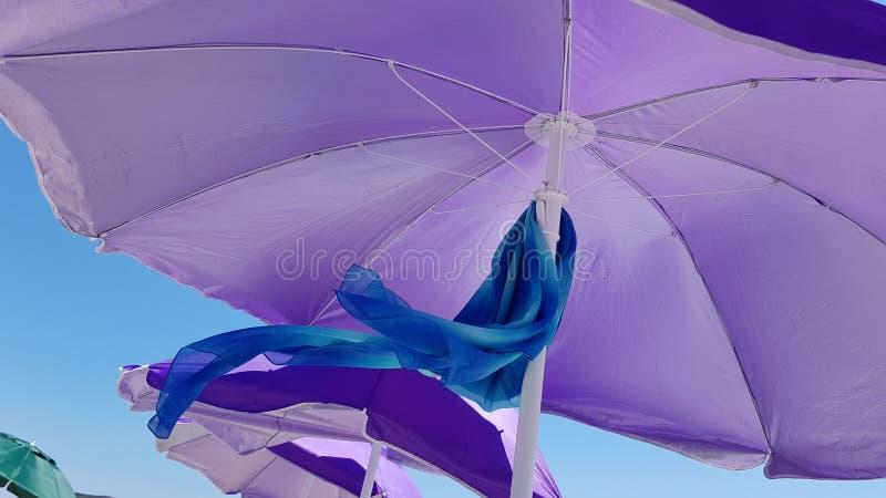 在紫罗兰色遮阳伞下的波浪蓝色纺织品围巾在天空蔚蓝背景 免版税库存图片