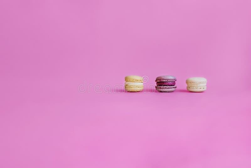 在紫色背景的三个蛋白杏仁饼干 免版税库存照片
