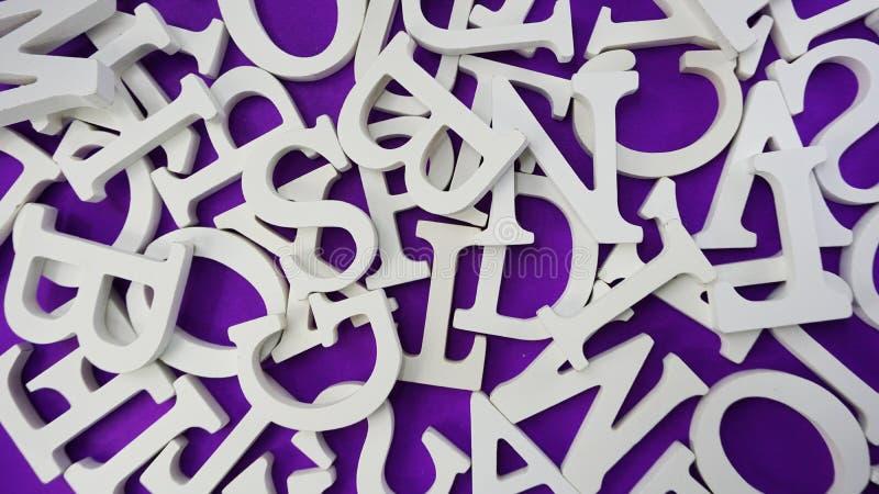 在紫色背景的任意白色木字母表信件 库存图片