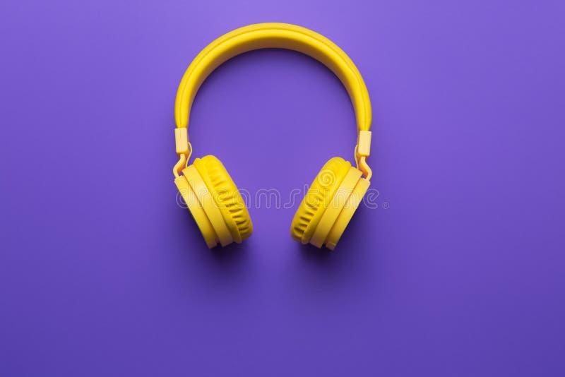 在紫色背景的黄色耳机 概念电吉他例证音乐 免版税图库摄影