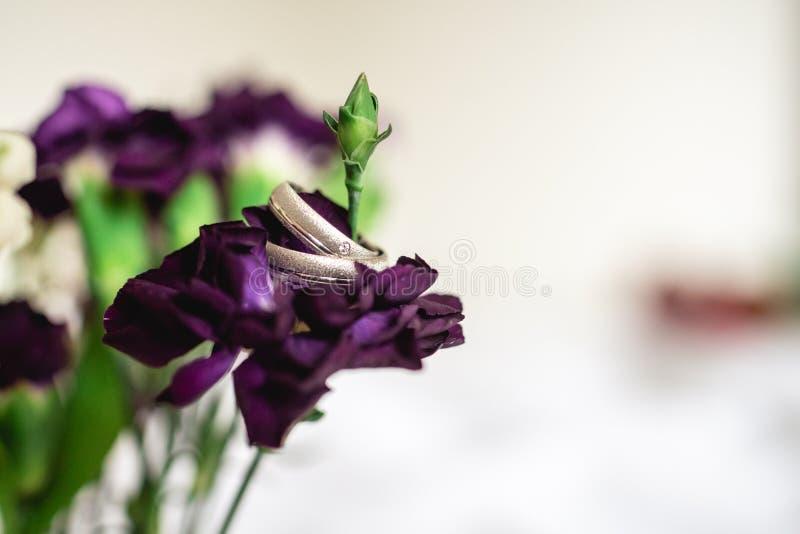 在一朵紫色花的结婚戒指 免版税库存图片