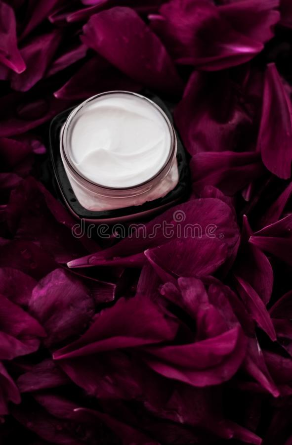 在紫色花瓣背景,皮肤的自然科学的敏感skincare润肤霜奶油 免版税库存图片