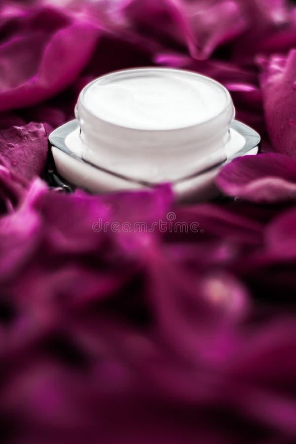在紫色花瓣背景,皮肤的自然科学的敏感skincare润肤霜奶油 库存图片