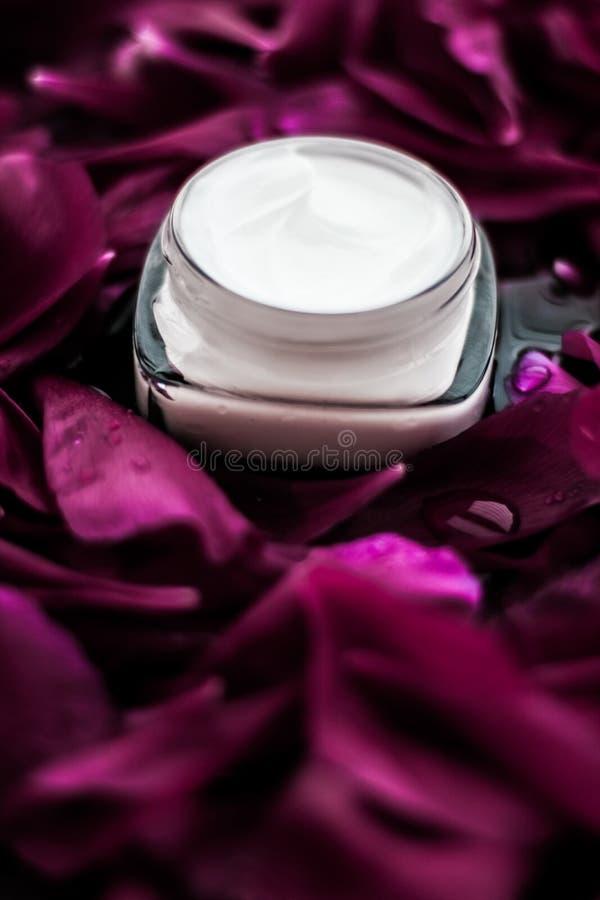 在紫色花瓣背景,皮肤的自然科学的敏感skincare润肤霜奶油 库存照片