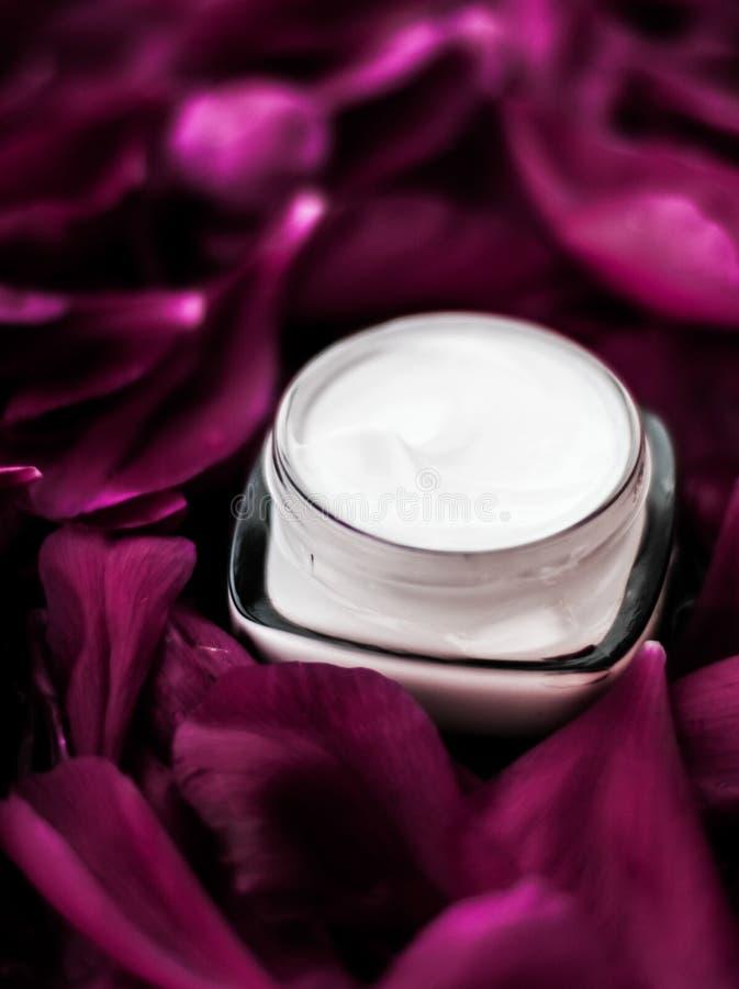 在紫色花瓣背景,皮肤的自然科学的敏感skincare润肤霜奶油 免版税图库摄影
