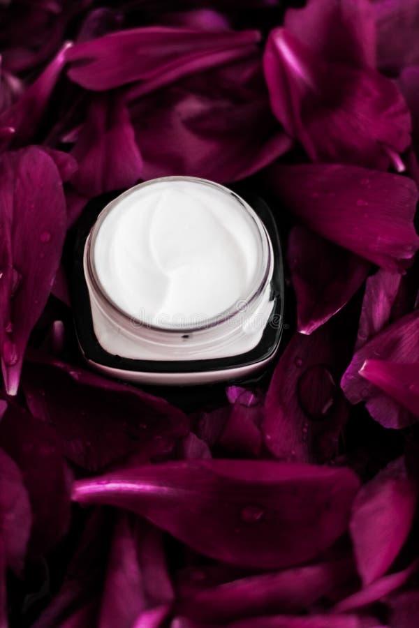 在紫色花瓣背景,皮肤的自然科学的敏感skincare润肤霜奶油 免版税库存照片