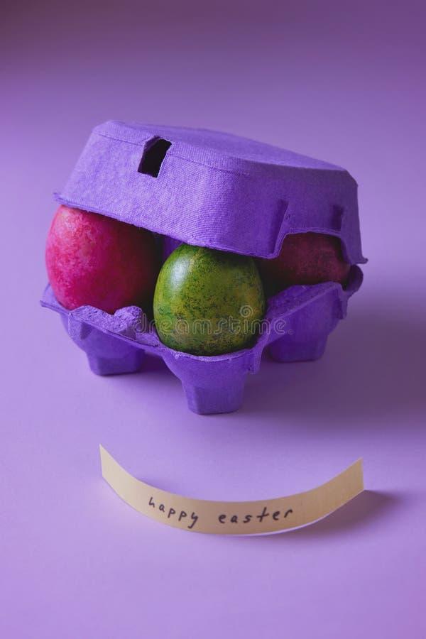 在紫色蛋盒的五颜六色的复活节彩蛋 免版税图库摄影