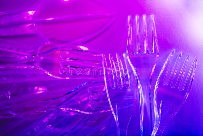 在紫色霓虹灯的塑料透明利器 免版税库存图片