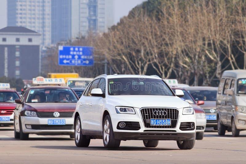 在繁忙的交通,伊吾,中国的白色奥迪Q5 图库摄影