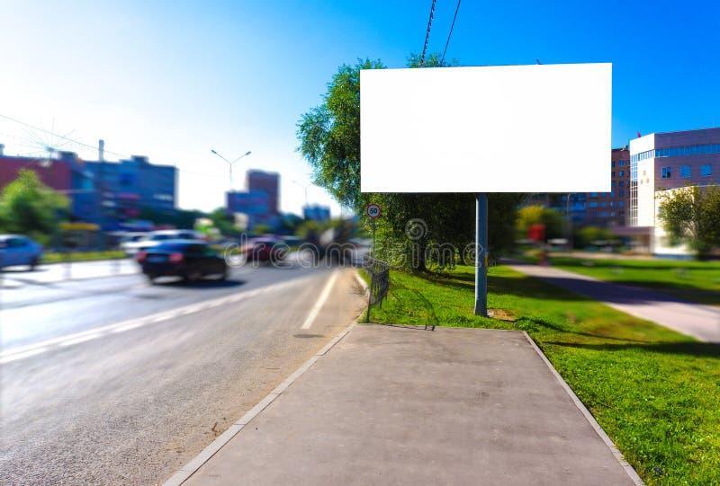 在繁忙的路的空的空白的广告牌,嘲笑  免版税库存图片