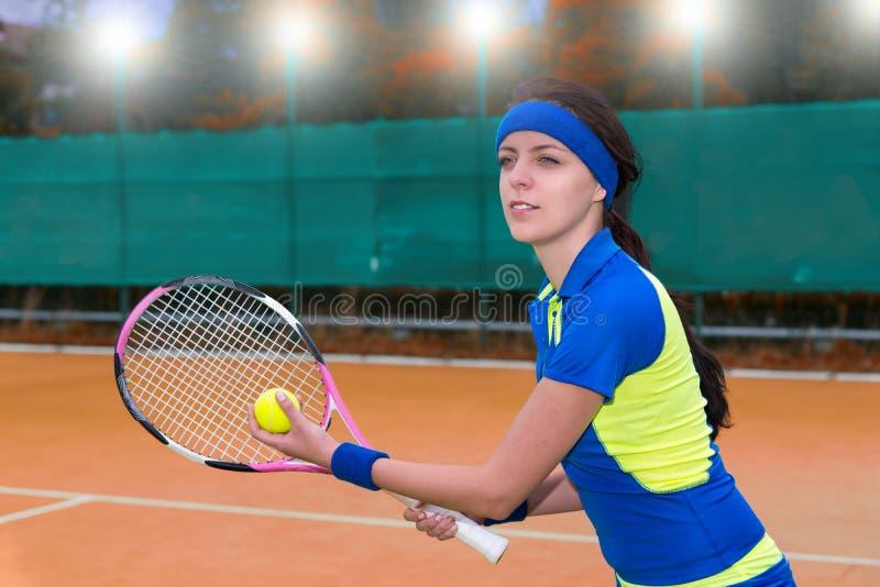 在红土网球场backg的美丽的年轻女性网球员服务 图库摄影