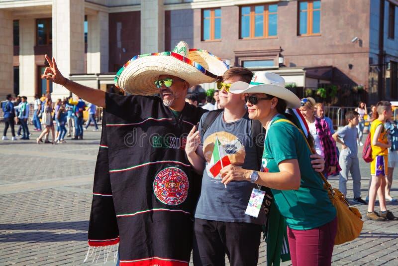 在红场的墨西哥足球迷在莫斯科 著名墨西哥阔边帽和雨披 橄榄球世界杯 免版税图库摄影