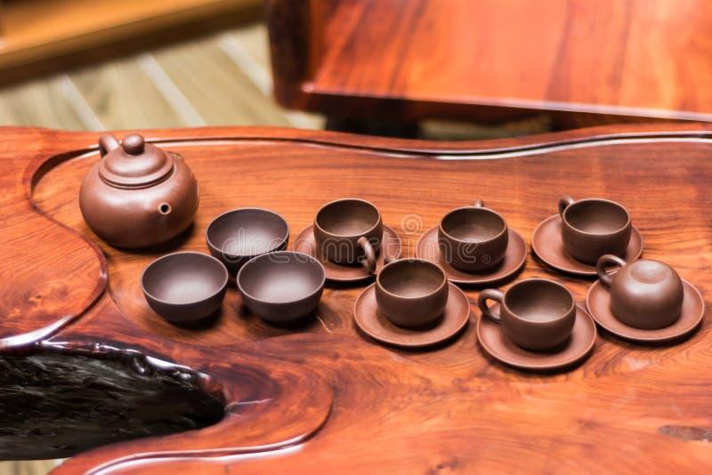 在红木茶几上的黏土茶壶 免版税库存图片