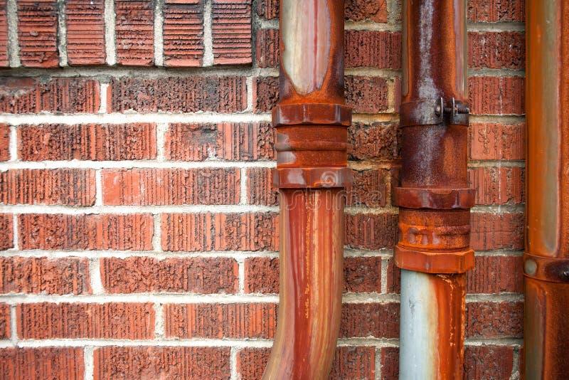 在红砖墙壁上的生锈的金属管子 库存图片