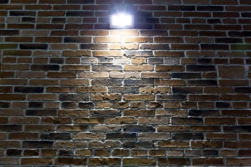 在红砖墙壁上的聚光灯在晚上 免版税图库摄影