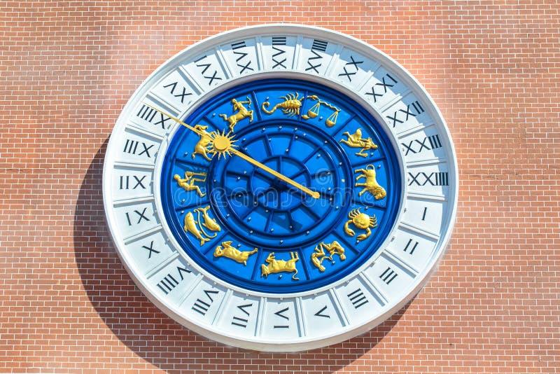 在红砖墙壁上的葡萄酒罗马黄道带时钟 库存照片
