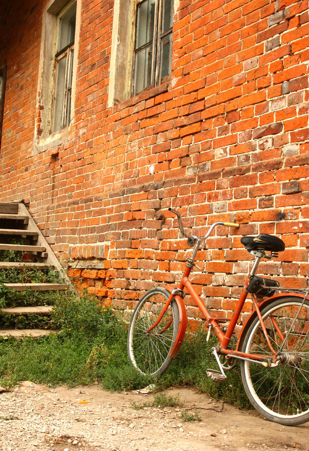 在红砖墙壁背景的老自行车  库存图片
