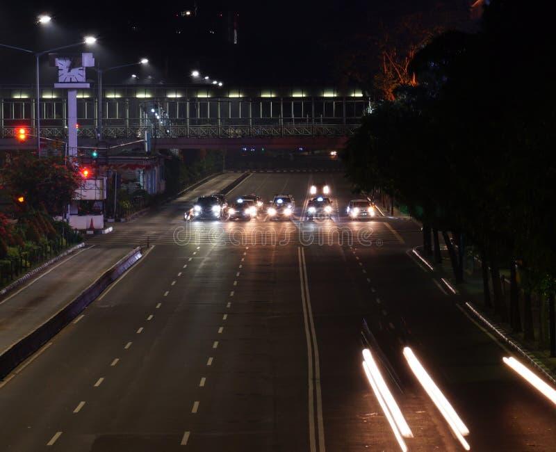 在红绿灯的汽车中止在晚上 免版税库存照片