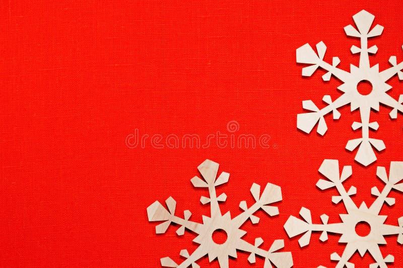 在红色亚麻制自然表面五颜六色的欢乐背景的木雪花与文本的空间 库存图片