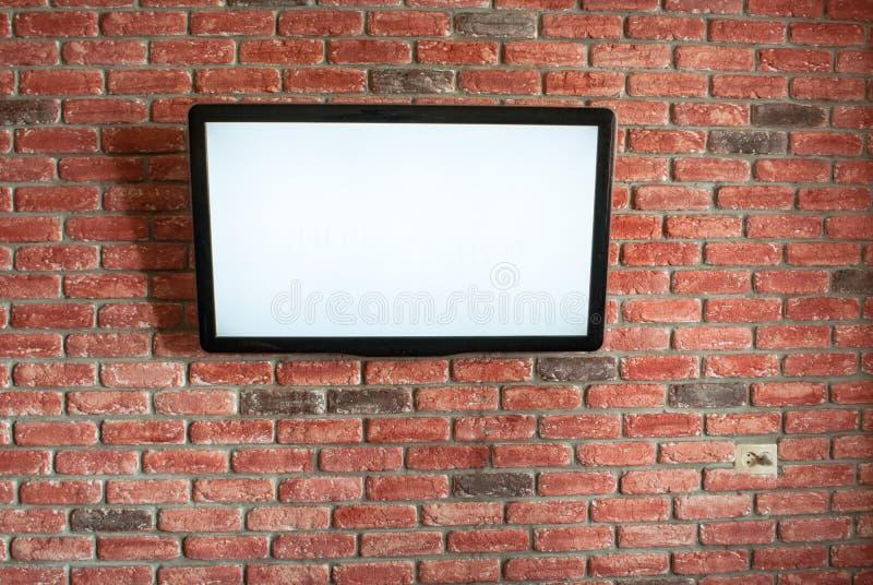 在红色内部砖墙上是白色屏幕电视 免版税图库摄影