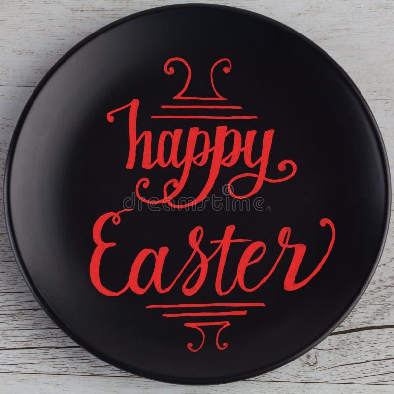 在红色写的愉快的复活节手字法在黑色的盘子和wh 免版税库存照片