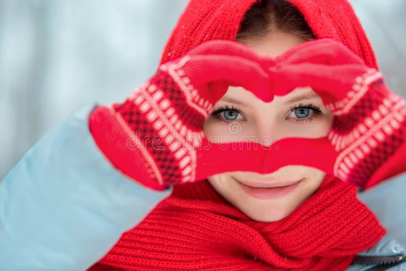 在红色冬天手套的妇女手 心脏标志形状的生活方式和感觉概念 免版税图库摄影