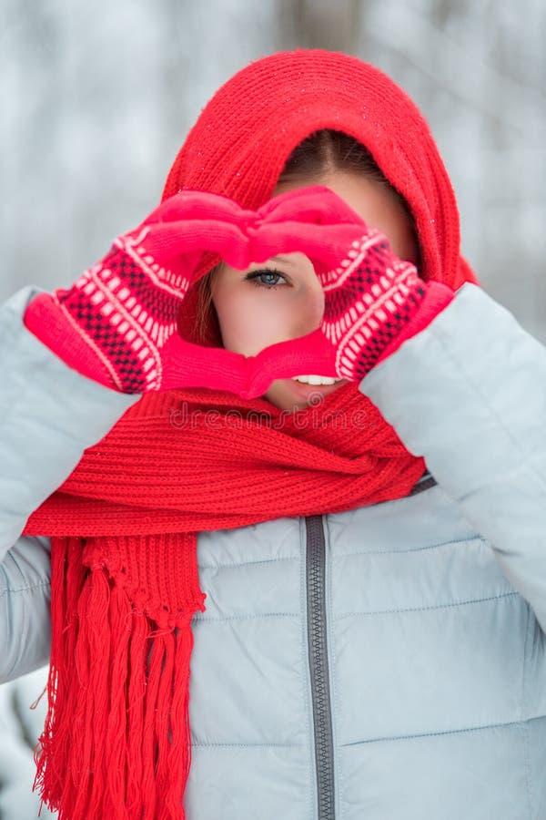 在红色冬天手套的妇女手 心脏标志形状的生活方式和感觉概念 库存照片