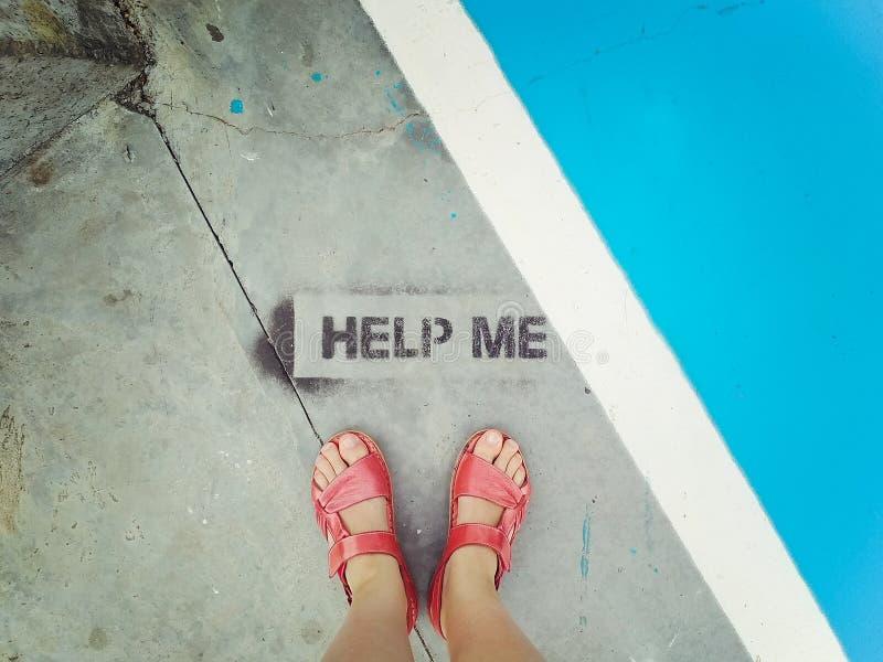 在红色凉鞋的妇女的脚在题字对面-帮助我 在视图之上 概念-迷茫的妇女或失去的游人 库存图片