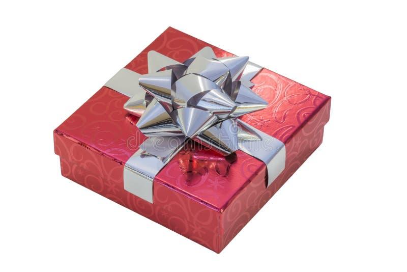在红色包裹的礼物盒仿造了与发光的银色丝带的纸 免版税库存照片