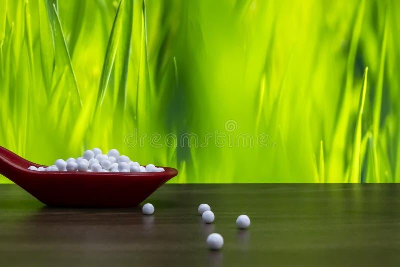 在红色匙子的同种疗法药片和有些小球传播了木表面上有绿色黄色背景 自然医学概念 免版税库存照片