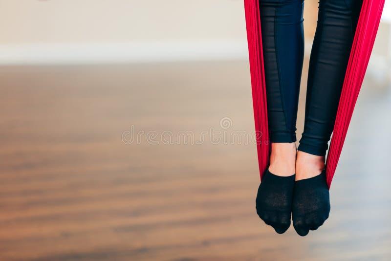 在红色吊床的女性腿在空中瑜伽班,关闭 免版税库存图片