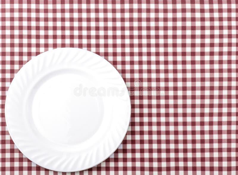 在红色和白色方格的织品桌布Backgro的白色板材 库存照片
