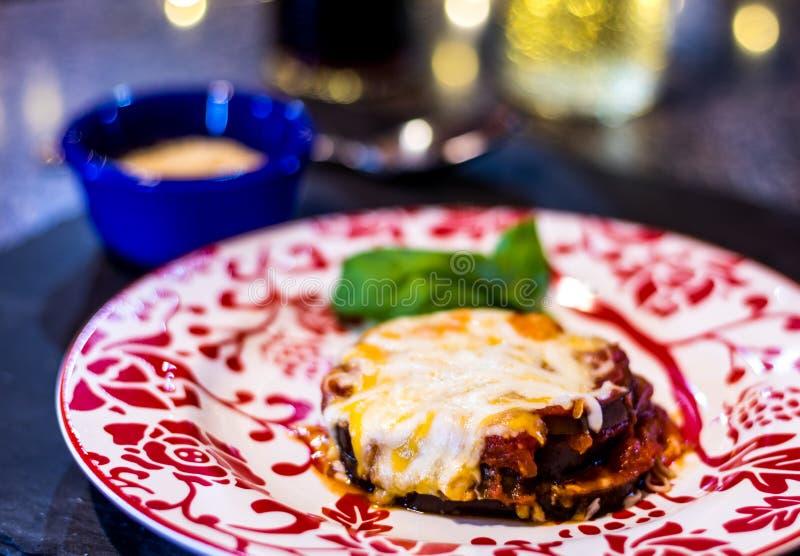 在红色和白色自由板材、的面筋没有鸡蛋或面包渣的被烘烤的茄子Parmagiana 免版税库存照片