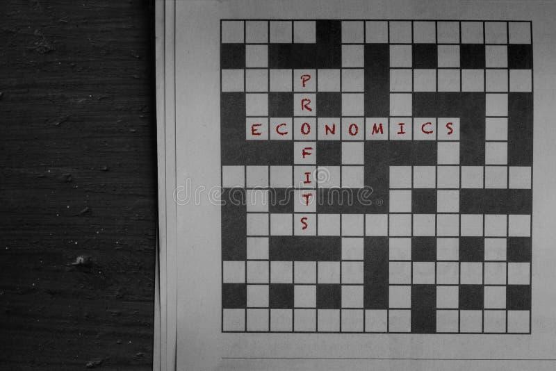 在红色和赢利写的经济,解答给报纸纵横填字游戏 库存照片