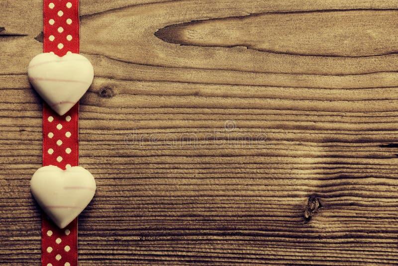 在红色圆点丝带,心形的巧克力-木背景 免版税库存照片