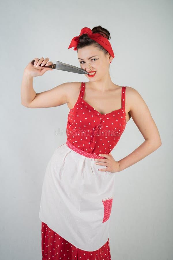 在红色圆点画报礼服和围裙的美好的少女身分,拿着一把大刀子和采摘她的牙,因为食物我 库存照片