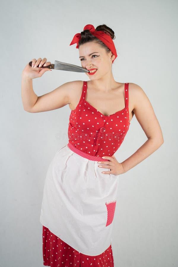 在红色圆点画报礼服和围裙的美好的少女身分,拿着一把大刀子和采摘她的牙,因为食物我 库存图片