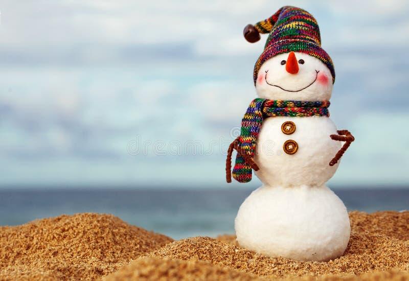 在红色圣诞老人帽子和太阳镜的圣诞节雪人在晴朗的海滩 免版税图库摄影