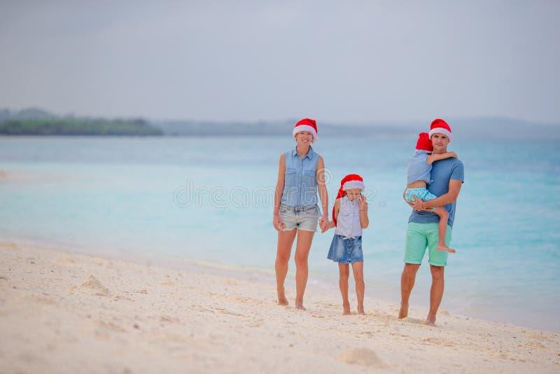 在红色圣诞老人帽子的愉快的家庭在热带海滩庆祝圣诞节的 免版税库存照片