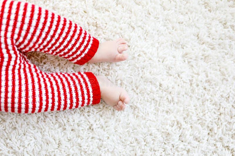 在红色圣诞老人长裤的婴孩身体特写镜头和腿在圣诞节 库存图片