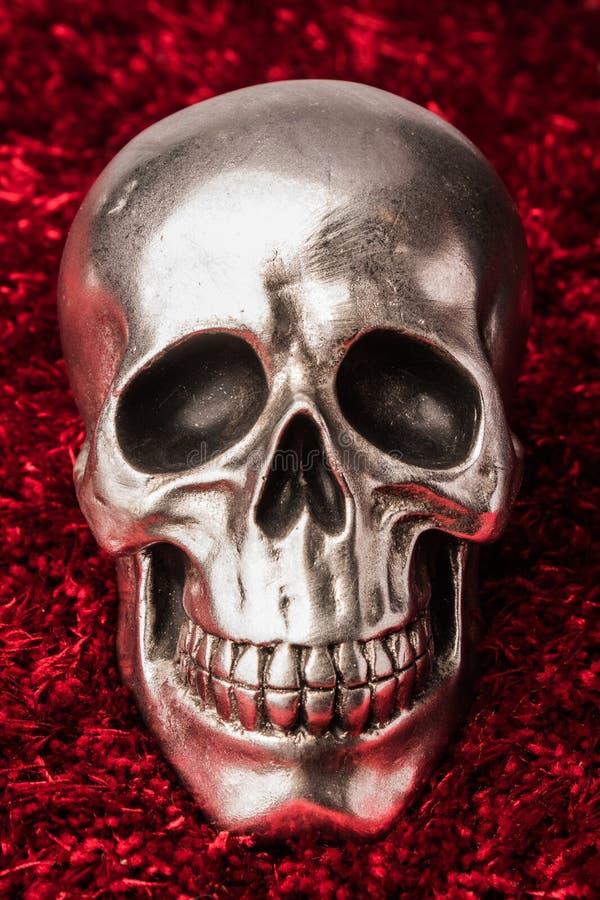 在红色地毯背景的金属头骨 库存照片