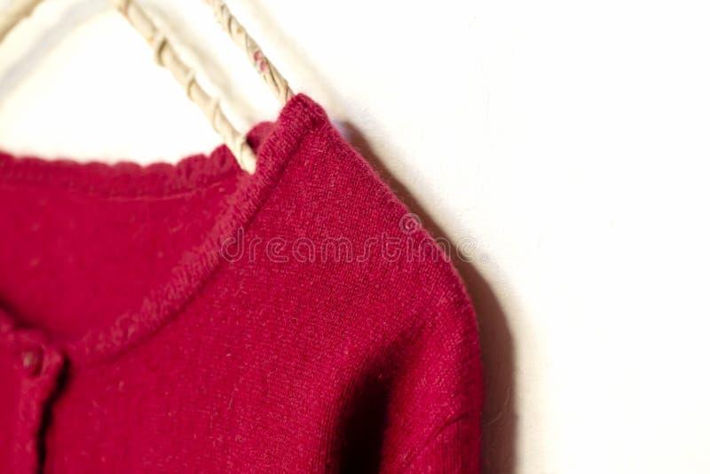 在红色垂悬的一件羊毛衫在白色背景的晒衣架 库存照片