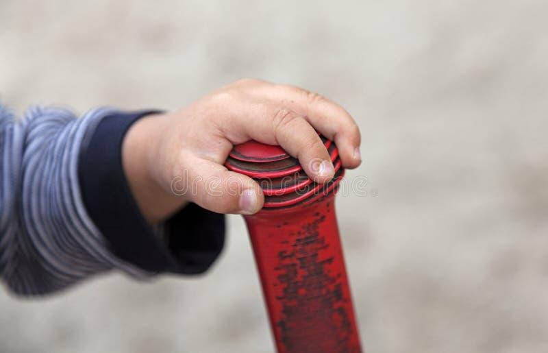在红色塑料把手的一只两岁的手 库存图片