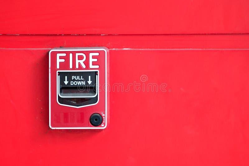 在红色墙壁上的火警开关 库存图片