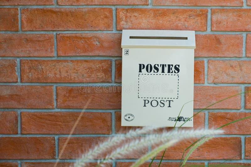 在红色墙壁上的白色木岗位箱子 免版税库存图片