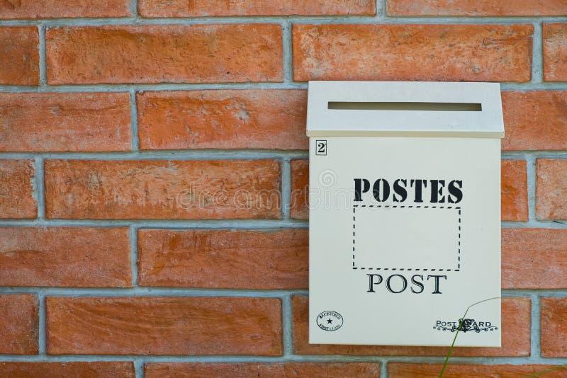 在红色墙壁上的白色木岗位箱子 库存照片