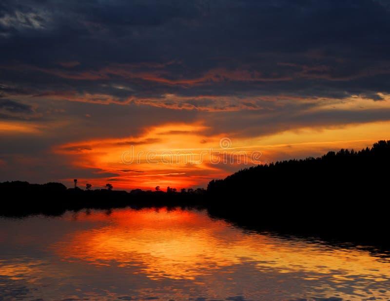 在红色天空的森林湖 库存图片