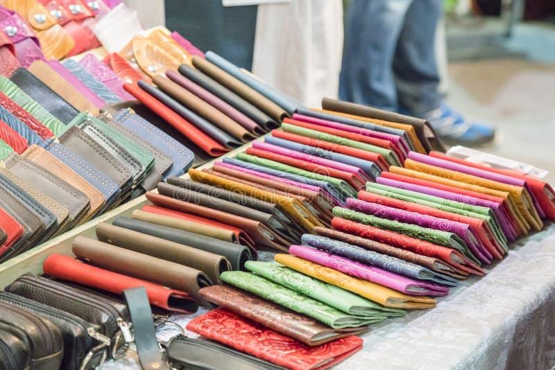 在红色天鹅绒的手工制造皮包 手工制造皮革钱包在家庭的待售购物 在一张木桌上的许多钱包 multico 图库摄影