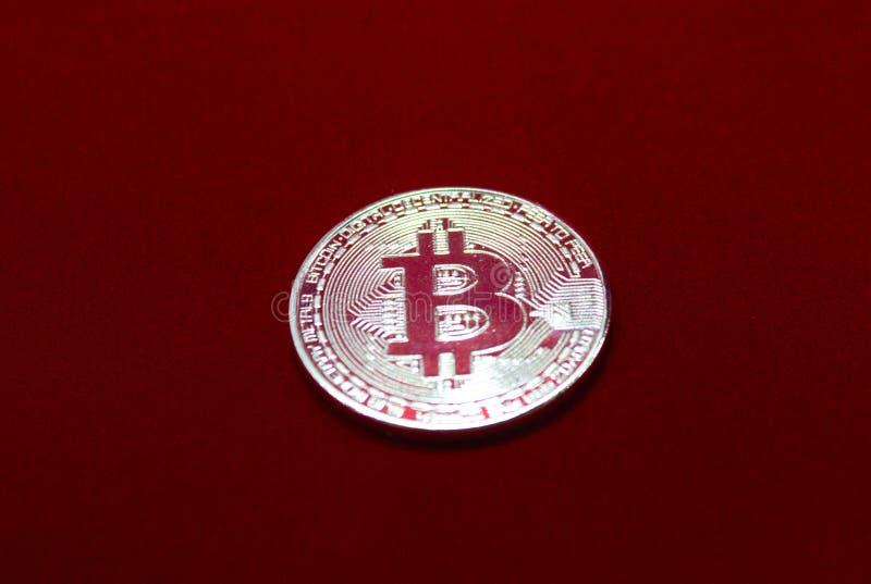 在红色天鹅绒背景的bitcoin 库存照片