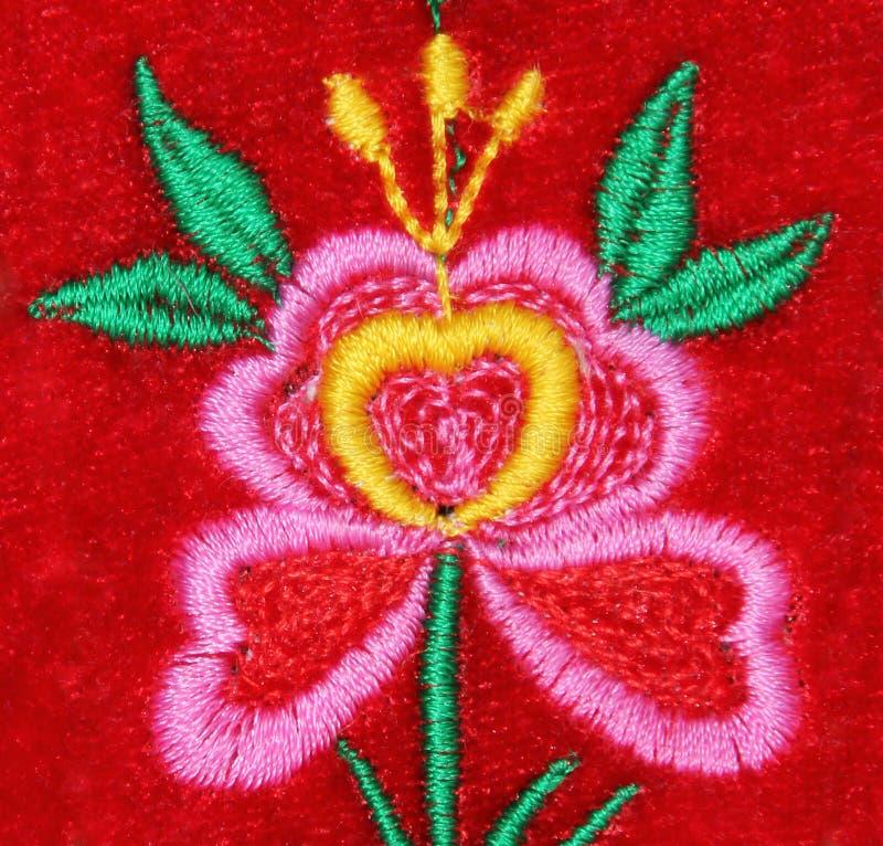 在红色天鹅绒的手工制造刺绣花 免版税库存照片